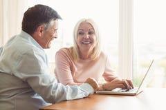 使用膝上型计算机的愉快的成熟夫妇 免版税库存图片