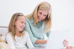 使用膝上型计算机的愉快的母亲和女儿 免版税库存照片