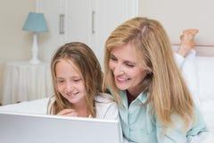 使用膝上型计算机的愉快的母亲和女儿 免版税库存图片