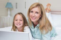 使用膝上型计算机的愉快的母亲和女儿 图库摄影