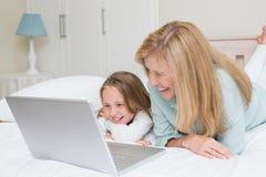 使用膝上型计算机的愉快的母亲和女儿 库存图片