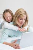 使用膝上型计算机的愉快的母亲和女儿 库存照片