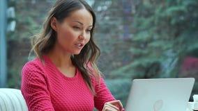使用膝上型计算机的愉快的白肤金发的妇女有电视电话会议在咖啡馆 图库摄影
