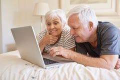 使用膝上型计算机的愉快的资深夫妇一起在床上 免版税库存图片