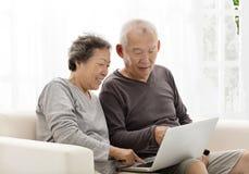使用膝上型计算机的愉快的资深夫妇在沙发 免版税库存图片