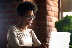 使用膝上型计算机的愉快的非裔美国人的妇女,聊天与朋友 免版税库存图片