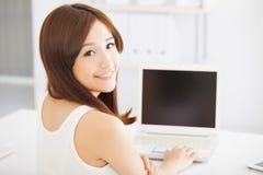 使用膝上型计算机的愉快的年轻亚裔妇女 免版税库存照片