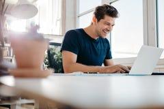 使用膝上型计算机的愉快的年轻商人在他的办公桌 免版税库存照片