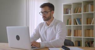 使用膝上型计算机的成人英俊的白种人商人特写镜头画象和看照相机在办公室户内 影视素材