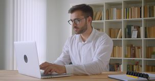 使用膝上型计算机的成人英俊的白种人商人特写镜头画象在办公室户内 股票视频