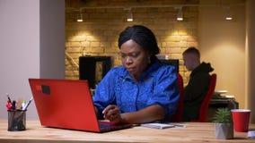 使用膝上型计算机的成人非裔美国人的女实业家特写镜头射击和喝咖啡在办公室户内 股票视频