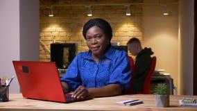 使用膝上型计算机的成人非裔美国人的女实业家特写镜头射击和看微笑的照相机在办公室 影视素材