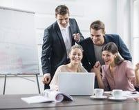 使用膝上型计算机的成功的年轻商人在会议 免版税库存照片
