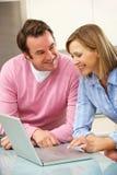 使用膝上型计算机的成熟夫妇在国内厨房里 免版税库存图片