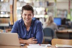 使用膝上型计算机的成熟男学生画象在图书馆 免版税库存图片