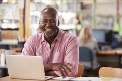 使用膝上型计算机的成熟男学生画象在图书馆 图库摄影