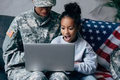 使用膝上型计算机的战士和孩子 库存照片