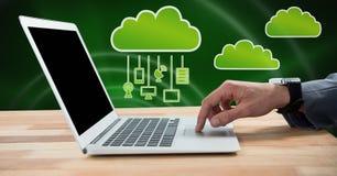 使用膝上型计算机的手有云彩象和垂悬的连接设备和绿色背景的 免版税库存照片