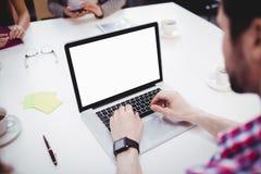 使用膝上型计算机的执行委员大角度看法在会议室在创造性的办公室 库存图片