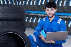 使用膝上型计算机的技工检查轮胎 免版税库存照片