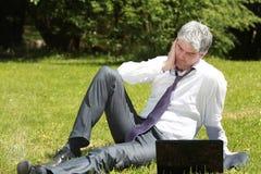 使用膝上型计算机的担心的商人在草甸 图库摄影