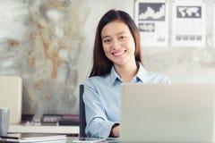 使用膝上型计算机的新一代亚裔女商人在办公室 库存照片