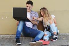 使用膝上型计算机的新夫妇 免版税库存照片