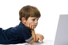 使用膝上型计算机的新男孩 免版税库存图片