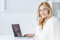 使用膝上型计算机的时髦的美丽的微笑的女实业家在现代光 免版税库存图片