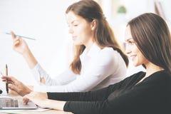 使用膝上型计算机的有吸引力的businessladies在工作场所 免版税库存图片