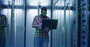 使用膝上型计算机的有胡子的IT工程师在服务器屋子里 库存照片