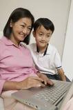 使用膝上型计算机的母亲和儿子在客厅 免版税库存图片