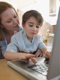 使用膝上型计算机的母亲和儿子在表 免版税库存照片