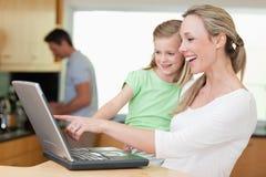 使用膝上型计算机的母亲和女儿 免版税图库摄影