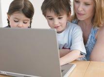 使用膝上型计算机的母亲和孩子在表 免版税库存图片