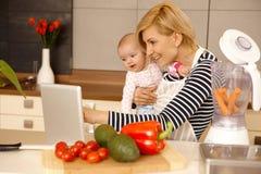 使用膝上型计算机的母亲和婴孩在厨房 免版税库存图片