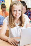 使用膝上型计算机的母台中国小学生在计算机类 免版税图库摄影