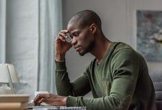使用膝上型计算机的沉思非裔美国人的人,当工作时 免版税库存照片