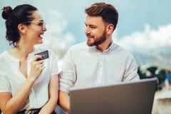 使用膝上型计算机的浪漫夫妇 在膝上型计算机的观看的图片,当旅行,由一种旅游海手段的港口时 库存图片