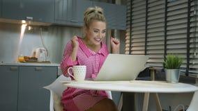 使用膝上型计算机的激动的妇女在厨房 股票录像