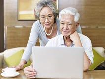 使用膝上型计算机的爱恋的资深亚洲夫妇 免版税库存照片