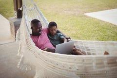 使用膝上型计算机的父亲和儿子,当放松在吊床时 库存图片