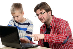 使用膝上型计算机的父亲和儿子 免版税库存照片