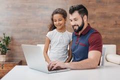 使用膝上型计算机的父亲和女儿,当在家时坐在桌 免版税库存照片