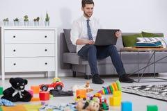 使用膝上型计算机的父亲 免版税库存图片