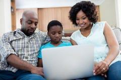 使用膝上型计算机的父母和儿子在客厅 免版税库存照片