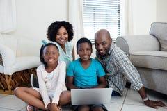 使用膝上型计算机的父母和他们的孩子画象在客厅 免版税库存照片