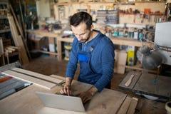 使用膝上型计算机的现代木匠 免版税图库摄影