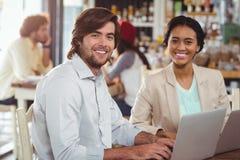 使用膝上型计算机的男人和妇女在会议期间 免版税库存图片