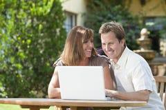 使用膝上型计算机的男人&妇女夫妇在庭院里 免版税图库摄影